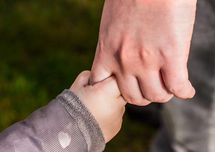 A childs hand holding an adults hand