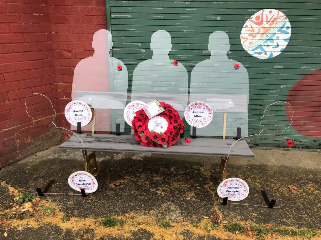 Three silhouettes with a commemoration wreath