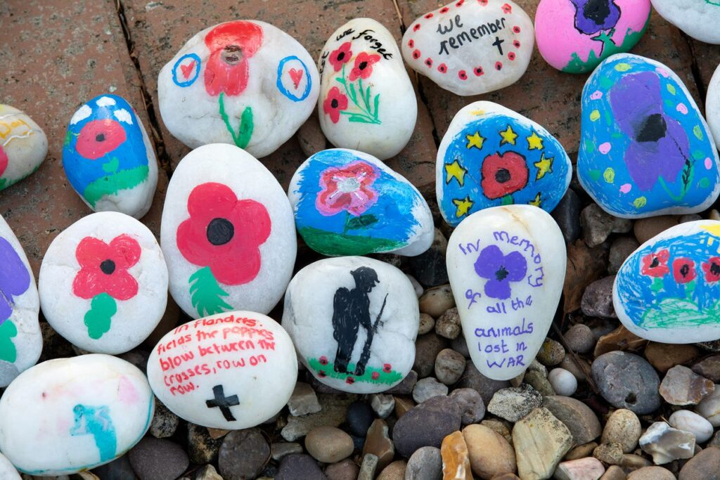 A selection of stones decorated with poppy and remembrance designs